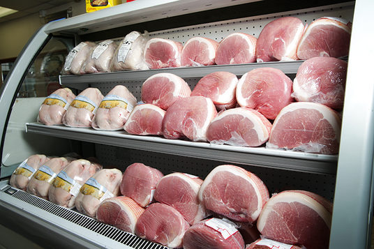 Gammon and fresh chickens in a display cabinet